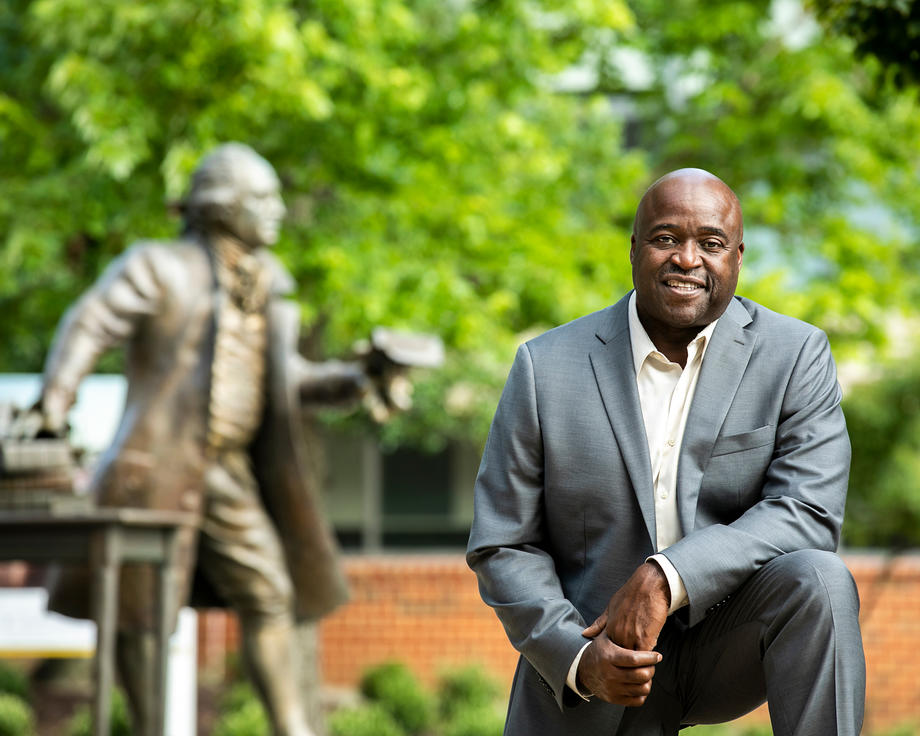 Gregory Washington environmental portrait in front of the statue of George Mason. Gregory Washinton inspires the Mason Nation to show patriotism through actions of inclusion and diversity.